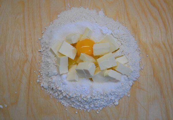 Mettete sulla spianatoia tutti gli ingredienti della pasta frolla. La farina a fontana con al centro lo zucchero, il burro tagliato a tocchetti, la fecola, l'uovo e il lievito.