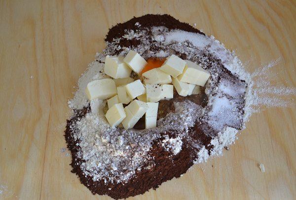 Preparate la pasta frolla mescolando farina, zucchero, burro, uova, cacao e lievito. Formate un panetto, avvolgetelo nella pellicola e mettetelo in frigo.