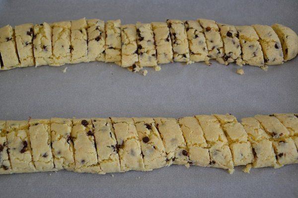 Estraete la teglia dal forno, lasciate raffreddare 2 minuti e con un coltello tagliate delle fette in diagonale di circa 2 cm. Stendete i biscotti nella teglia.