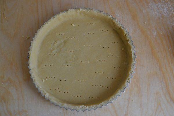 Imburrate e infarinate lo stampo per crostata e formate il fondo della crostata con la pasta frolla.