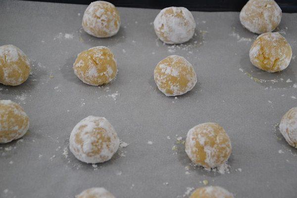 Rotolate le palline nello zucchero a velo e mettetele sulla placca da forno su un foglio di carta da forno.