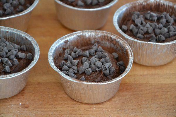 Versateci l'impasto riempiendoli per massimo 2/3 e decorate la superficie con gocce di cioccolato.