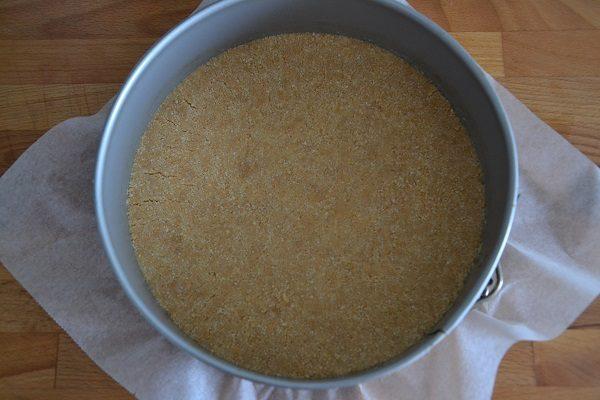 Versate il composto sulla base di uno stampo apribile, a cerniera e livellatelo con il dorso di un cucchiaio. Mettete in frigo.