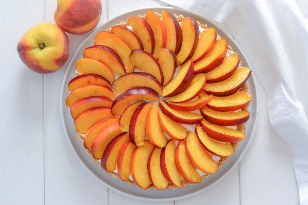Versate la crema al mascarpone sulla base di biscotti e decorate con pesche o altra frutta a scelta.