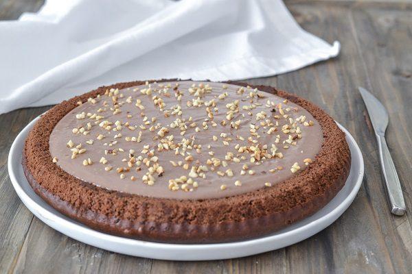 Riempite la crostata con la crema alle nocciole e decorate con granella di nocciole.