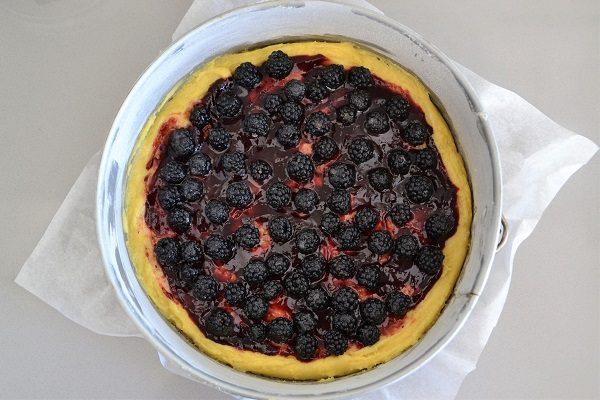 Mescolate i frutti di bosco con il cucchiaio di zucchero e aggiungeteli sulla superficie della torta.