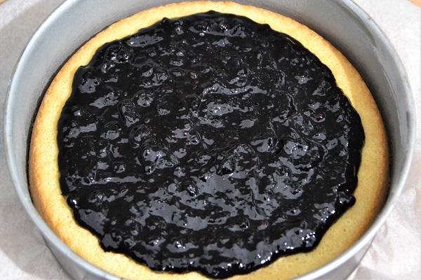 Trascorsi 20 minuti, estraete dal forno la torta versata e mettete al centro il ripieno ai mirtilli, cercando di non andare troppo vicino ai bordi dello stampo.