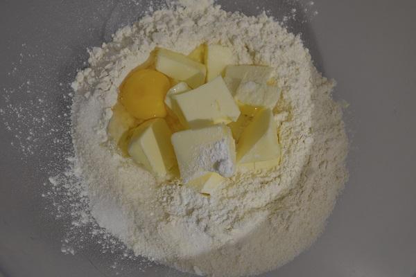Mettete la farina sulla spianatoia o in una ciotola grande e mettete al centro lo zucchero, il burro a pezzetti, l'uovo, la fecola e il pizzico di lievito.