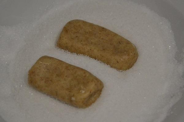 Formate dei filoncini e tagliateli a pezzetti di 6-7 cm col coltello per formare i biscotti. Schiacciateli leggermente con le mani e passateli nello zucchero semolato.