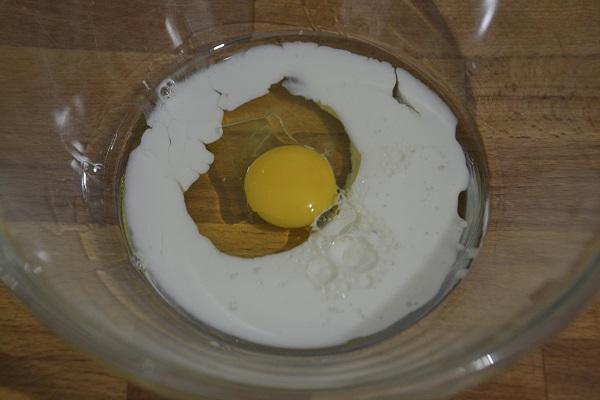 Per preparare i biscotti da latte senza burro mettete l'uovo, il latte e l'olio di semi in una ciotola capiente.