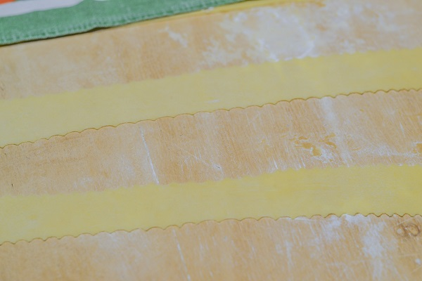 Coprite la sfoglia con un canovaccio pulito per evitare che si secchi e tagliate qualche striscia di impasto per volta usando una rotella tagliapasta. Potete realizzare delle strisce, rombi o pezzi irregolari.