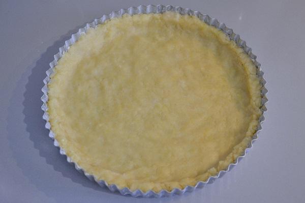 Stendete con le mani l'impasto sulla base dello stampo e aggiungete la crema all'uva.