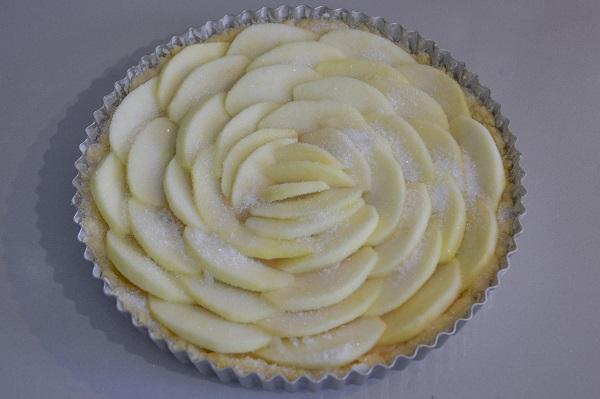 Decorate la torta con le fettine di mela. Aggiungete sulla superficie uno o due cucchiai di zucchero.