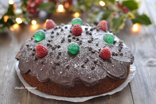 Decorate la torta di Natale con ciliegie candite, gocce di cioccolato, lamponi e perle di zucchero.