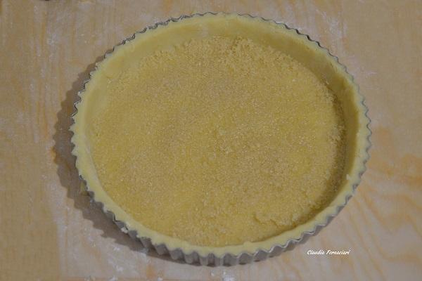 Bucherellate il fondo della crostata con i rebbi di una forchetta e stendete il pangrattato in modo omogeneo.