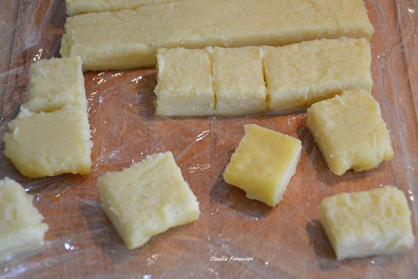 Trascorso il tempo necessario, rovesciate la crema su un foglio di pellicola trasparente, rimuovete delicatamente la carta da forno e ritagliate dei cubi o rombi.